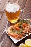 Taza de cerveza y camarones asados a la parrilla Imágenes de archivo libres de regalías