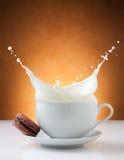 Taza de chapoteo de la leche con el macaron Imagen de archivo