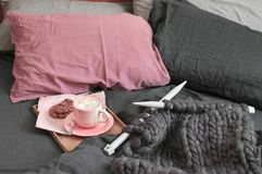 Taza de chocolate caliente con las galletas y de hacer punto abultado en cama fotos de archivo libres de regalías