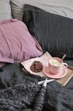 Taza de chocolate caliente con las galletas y de hacer punto abultado en cama foto de archivo libre de regalías