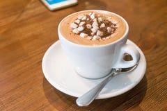 Taza de chocolate caliente con las melcochas y de smartphone en la tabla de madera foto de archivo