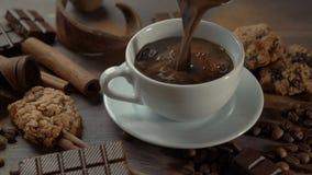 Taza de chocolate caliente con los palillos de canela, las rebanadas del chocolate y las galletas en la tabla de madera vieja almacen de video