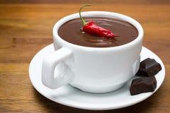 Taza de chocolate caliente con pimientas de chile en un fondo de madera Foto de archivo