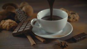 Taza de chocolate caliente, de palillos de canela, de galletas y de chocolate en la tabla de madera almacen de metraje de vídeo