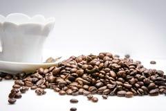 Taza de coffe al costado con las habas del coffe en el fondo blanco Imagen de archivo