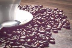 Taza de coffe al costado con las habas del coffe en la tabla al costado con la cuchara Imagen de archivo libre de regalías
