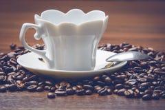 Taza de coffe al costado con las habas del coffe en la tabla de madera al costado con la cuchara Foto de archivo