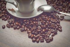 Taza de coffe al costado con las habas del coffe en la tabla de madera al costado con la cuchara Foto de archivo libre de regalías