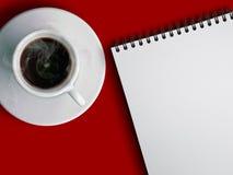 Taza de coffe y de cuaderno calientes Imágenes de archivo libres de regalías
