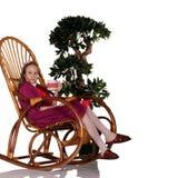 Taza de consumición de la muchacha de té que se sienta en mecedora Imagen de archivo