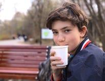 Taza de consumición del muchacho del adolescente de café en el cierre de papel del vidrio encima de la foto Imagen de archivo