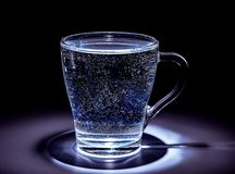 Taza de cristal con la agua fr?a en una tonalidad oscura Iluminaci?n superior imágenes de archivo libres de regalías