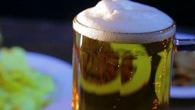 Taza de cristal con la cerveza ligera espumosa en un fondo negro metrajes