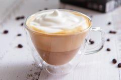 Taza de cristal con latte del coffe en los tableros blancos Imágenes de archivo libres de regalías