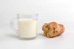 Taza de cristal con leche y una rebanada de pan Fotografía de archivo
