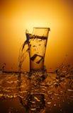 Taza de cristal de estallido con agua que rompe sobre fondo anaranjado Fotografía de archivo