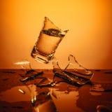 Taza de cristal de estallido con agua que rompe sobre fondo anaranjado Fotos de archivo libres de regalías
