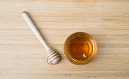 Taza de cristal de miel y de cazo de la miel en fondo de madera Imagen de archivo