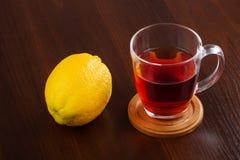 Taza de cristal de té caliente y de un limón Imágenes de archivo libres de regalías