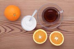 Taza de cristal de té con el azúcar y la naranja en la tabla Fotos de archivo libres de regalías