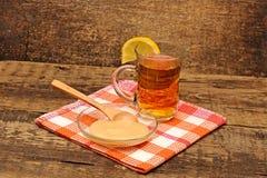 Taza de cristal de té con la miel Imagenes de archivo