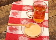 Taza de cristal de té con la miel Foto de archivo libre de regalías