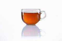 Taza de cristal de té negro en el fondo blanco Fotos de archivo