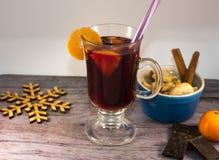 Taza de cristal de vino reflexionado sobre con las especias y las galletas en la tabla Foto de archivo