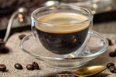 Taza de cristal del café express con el grano de café foto de archivo