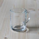 Taza de cristal en una tabla de madera Imagen de archivo