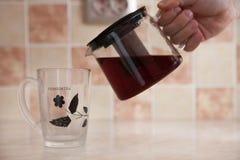 Taza de cristal de la tetera y del vidrio con té en la tabla Foto de archivo