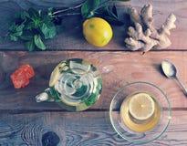 Taza de cristal de la tetera y del vidrio de té con el jengibre y limón y menta Fotografía de archivo