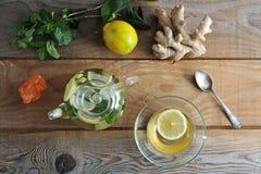 Taza de cristal de la tetera y del vidrio de té con el jengibre y limón y menta Imágenes de archivo libres de regalías