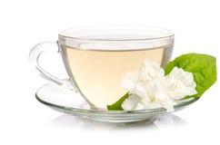 Taza de cristal de té con las flores del jazmín Imágenes de archivo libres de regalías