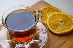 Taza de cristal de té con las rebanadas anaranjadas en una bandeja de madera imagenes de archivo