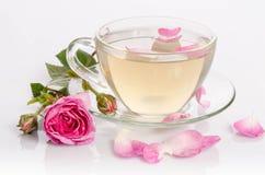 Taza de cristal de té con las rosas y los pétalos Imágenes de archivo libres de regalías