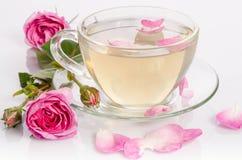 Taza de cristal de té con las rosas y los pétalos Foto de archivo libre de regalías