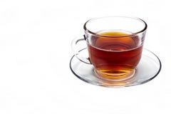 Taza de cristal transparente con té en un platillo aislado Foto de archivo libre de regalías
