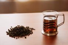 Taza de cristal y té vertido en la tabla Foto de archivo libre de regalías