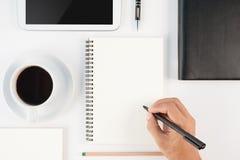 Taza de cuaderno caliente de la escritura de la mano del café y del hombre en el backgr blanco Foto de archivo
