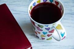 Taza de cuaderno del té y del papel foto de archivo