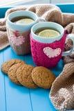 Taza de dos azules de té en suéter hecho punto con fieltro de los corazones Fotografía de archivo