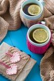 Taza de dos azules de té en suéter hecho punto con fieltro de los corazones Imagen de archivo libre de regalías