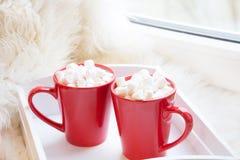 Taza de dos rojos de chocolate caliente con la melcocha en el alféizar blanco con la peletería para el concepto del día de fiesta Foto de archivo libre de regalías