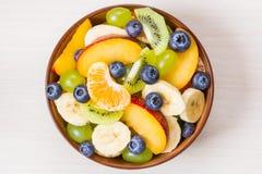 Taza de ensalada de fruta fresca en un fondo de madera Imagen de archivo