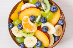 Taza de ensalada de fruta fresca en un fondo de madera fotografía de archivo