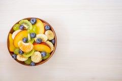 Taza de ensalada de fruta fresca en un fondo de madera Imagenes de archivo
