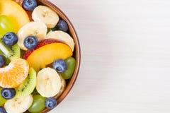 Taza de ensalada de fruta fresca en un fondo de madera Fotografía de archivo libre de regalías