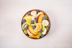 Taza de ensalada de fruta fresca en un fondo de madera Fotos de archivo