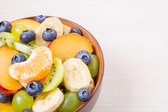 Taza de ensalada de fruta fresca en un fondo de madera imágenes de archivo libres de regalías